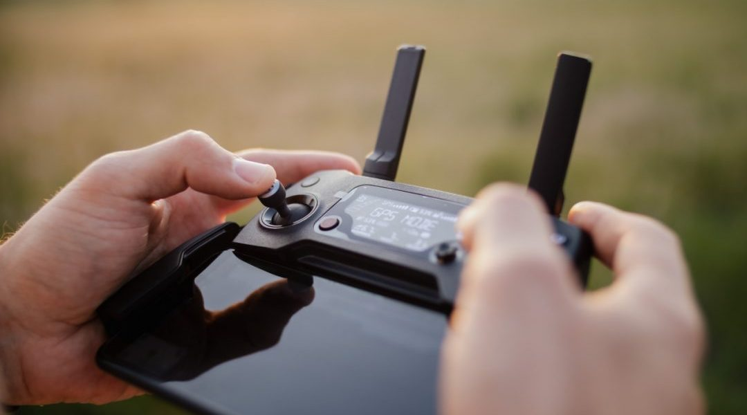 kaboompics_Man-holding-remote-controller-for-drones-flying-1080x675