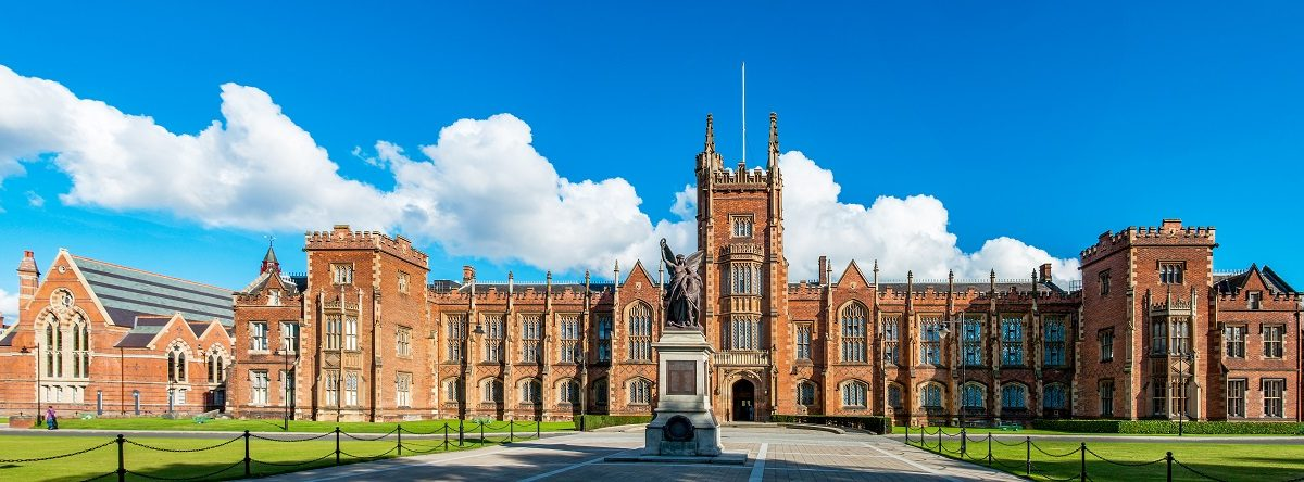 The Queen's University of Belfast with a grass lawn in sunset light.